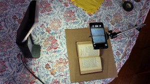 Digitization using cell phone camera, lamp, and snake clamp with universal cell phone mount. Glass from a picture frame laid upon the book keeps it flat enough for a satisfactory OCR. (credit: Aharon Varady, license: CC BY-SA)