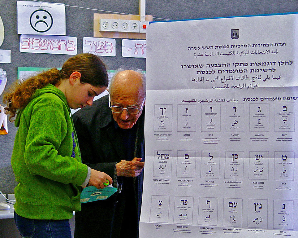 """Voting in Israel"" – Josef Tal is helped by his granddaughter (2003 polls). Photographed in a Jerusalem school. (credit: Etan J. Tal, license: CC BY)"