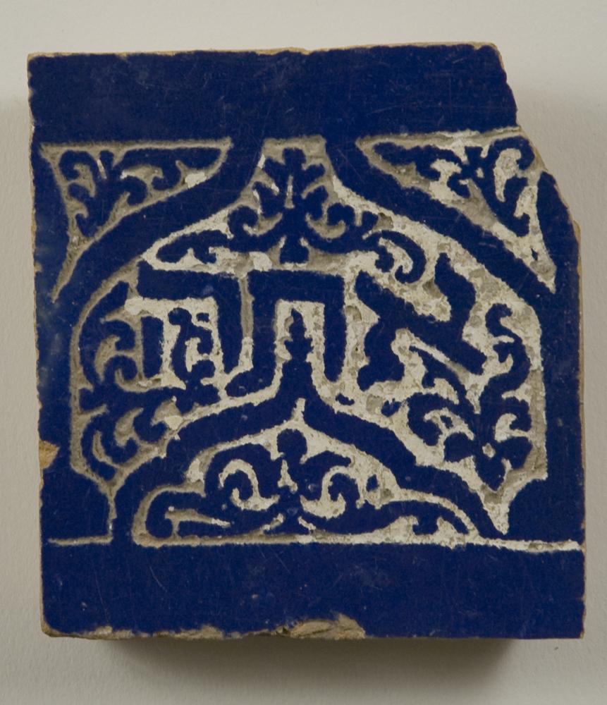 "אתה Synagogue tile decorated with Moorish motif and inscribed with the Hebrew word אתה ""atah"" (you), Morocco, 18th century. Blue and white ceramic tile with Moorish arch and floral motif; Original record notes that this tile came from a Moroccan synagogue. Possibly from ""baruch atah bevo'echa uvaruch ata btzetecha"" (ברוך אתה בבואך וברוך אתה בצאתך), Deuteronomy 28:6; cf. tiled inscriptions in Lazama synagogue, Marrakech. This tile is most likely from one of the four imperial cities: Fez, Meknes, Marrakesh, or Rabat. (From the Magnes Museum collection, Tile [77-275].)"
