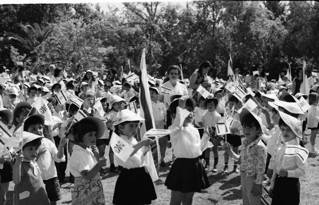 """גני הילדים בלוד חוגגיםאת יום העצמאות בגן העירוני"""" (credit: Mihael Almagor, 1973 or 1974, license: CC BY)"""