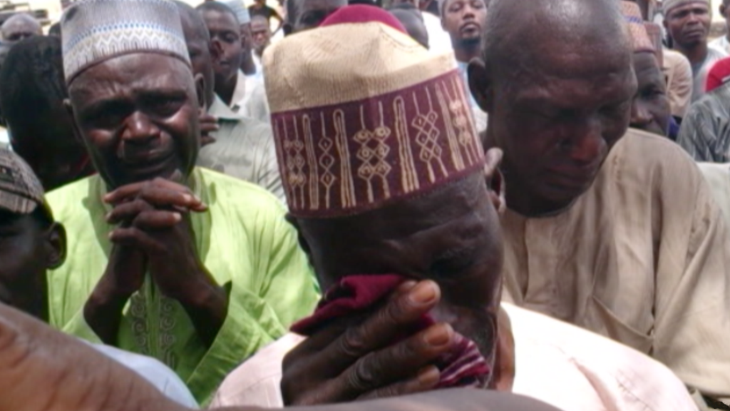 """""""Parents of some of the victims of the 2014 Chibok kidnapping mourn their losses"""" (credit: Voice of America, Public Domain)"""