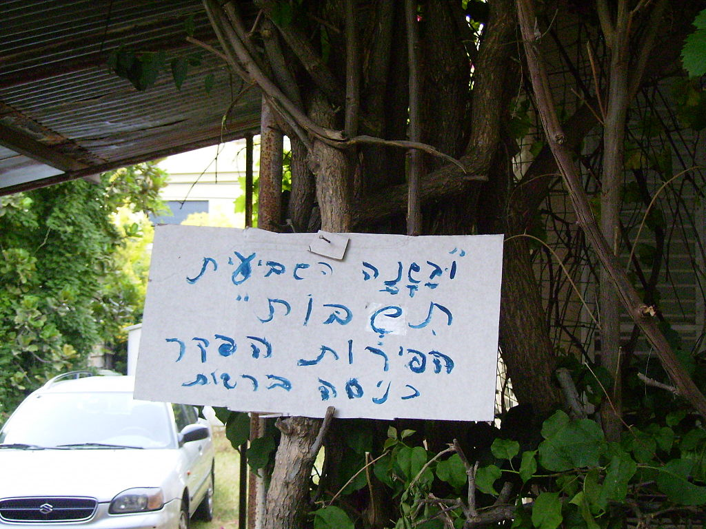 """Shmita sign."" A resident of Holon, Israel, announcing the fruits on the trees in his backyard are hefker (ownerless property) during the year of Shmita, and that anyone can enter and harvest them. עברית: תושב חולון מודיע כי הפירות על העצים בחצרו הם הפקר לרגל שנת שמיטה. (credit: Drork, Public Domain.)"