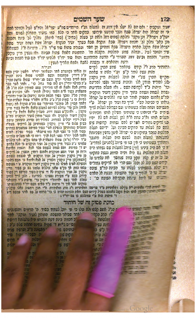 Image of a Google Books imaging technician inadvertently scanning their hand obscuring the commentary of Rabbi Isaiah Horowitz on the Shema.