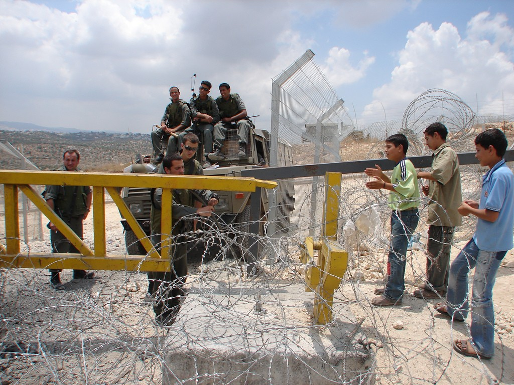 """Barrier Gate at Bil'in. The gate is the only means of entry for the villagers who have been separated from their farmland by the Israeli West Bank Barrier."""" (credit: Harry Pockets, license: CC BY-SA)"""