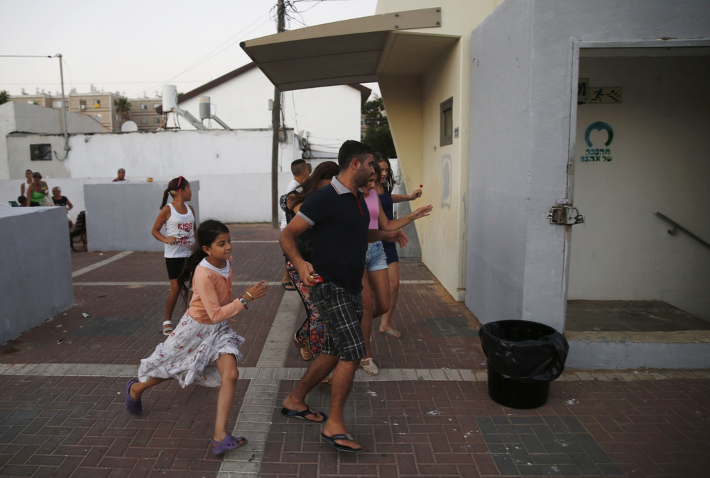 """Ashkelon residents run for shelter during a bomb alert"" (credit: B'tselem/Baz Ratner, license: CC BY)"
