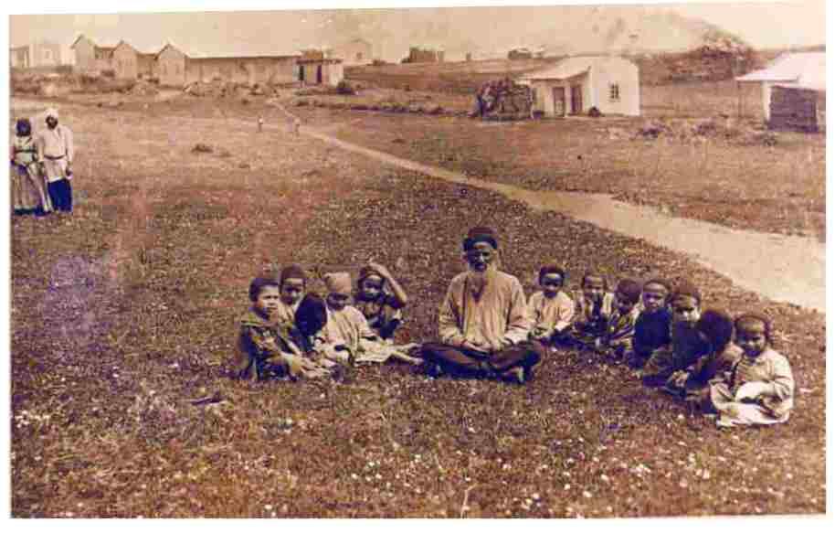 "Torah study, Hadera, Palestine"" Original name: ""חדרה בראשיתה - מורה ותלמידים צעירים לומדים תורה מתוך ספר אחד"" (between 1901 and 1911, Public Domain)"