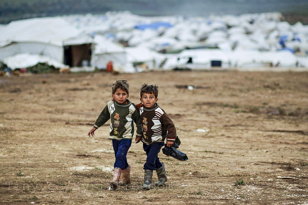 Syrian boys, whose family fled their home in Idlib, walk to their tent, at a camp for displaced Syrians, in the village of Atmeh, Syria, Monday, Dec. 10, 2012 (credit: Freedom House, license: CC BY)