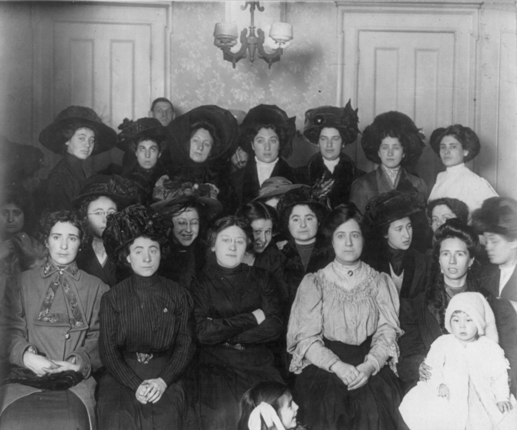 """Group of mainly female shirtwaist workers on strike, in a room, New York"" (January 1910)"