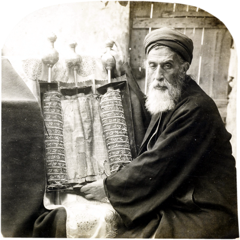 """Samaritan High Priest and Old Pentateuch, 1905"" Samaritan High Priest and Old Pentateuch, Nablus, West Bank. Part of a stereograph from Views of Palestine (1905). The text accompanying this image states ""We are looking into the eyes of the chief representative of a religious sect, one of the oldest and certainly smallest in the world...They claim that they are the lineal descendants of the Israelites of old, from a remnant that was left when the tribes were carried into Syrian captivity...There is no doubt but that they are the representatives of the Samaritans of the time of Christ, for whom the Jews had such a deadly hatred. Here is kept with jealous care this ancient copy of the Pentateuch which is before us - one of the very oldest copies in existence. We could not have seen it on any account except in the presence of this high priest."" (collection: J. Paul Getty Museum, credit: Keystone View Company, 1905)"