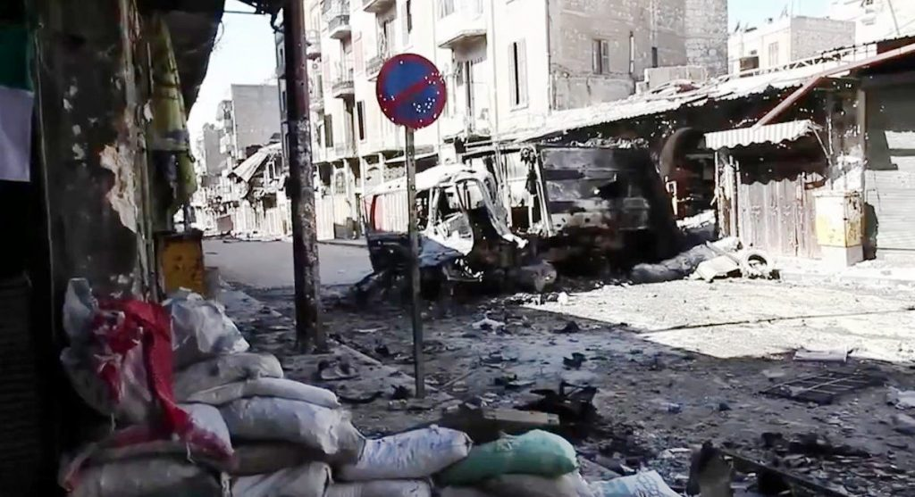 """Bombed out vehicles Aleppo during the Syrian civil war."" (credit: Voice of America News: Scott Bobb reports from Aleppo, Syria; license: PD)"