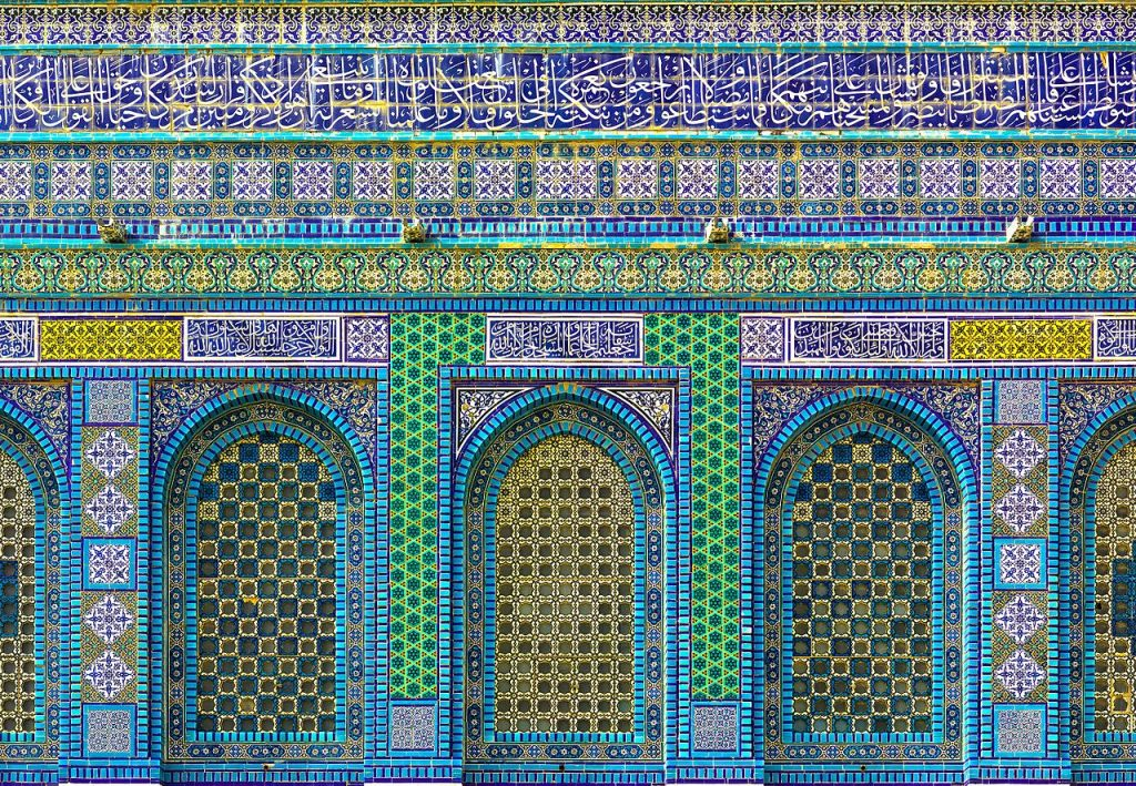Dome of the Rock (Arabic: مسجد قبة الصخرة‎, Hebrew: כיפת הסלע), (NE facade, panel detail with ceramic tiles on the Temple Mount in the Old City of Jerusalem. The tiles were added as part of the redecoration of the building ordered by Sultan Suleyman who sent a group of tile-makers from Istanbul to Jerusalem. They were led by Abdullah Tabrizi who signed the cut-tile inscription at the top of the drum with the date 952 AH/AD 1545-6 and the inscription above the north porch with the date 959 AH/AD 1551-2. The tile-makers used a range of techniques, including cut-tile work, cuerda seca, and under-glaze. (credit: Godot13, license: CC BY-SA)