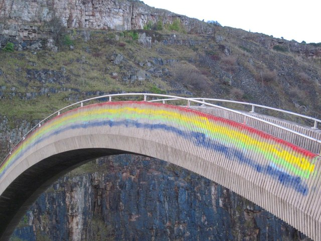 """Pont yr Enfys, Rainbow Bridge."" This bridge has colloquially been known as Rainbow Bridge since it was first built, but has recently been painted in (approximately) the colours of the rainbow. (credit: Ceri Thomas, license: CC BY-SA)"