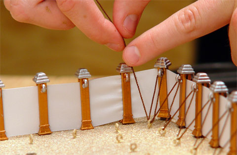 """After putting the posts in, hook the brown strings around the hooks on the bottom and the hooks on the post. You can start with either outside the fence or inside the fence."" from the Tabernacle Model Assembly Guide (GoodSeed International)"