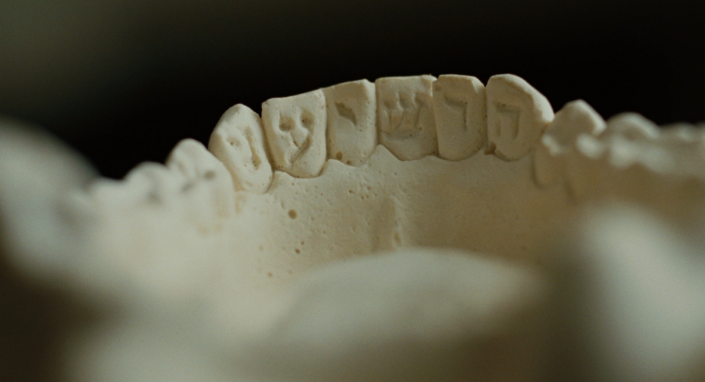 "a still frame from a segment of the film A SERIOUS MAN (dir. Coen Bros. 2009) showing the word הושיעני (hoShiaNi, ""save me"") inscribed in the teeth of a dental patient  (after Leviticus 24:20 שן תחת שן SheN taḥat SheN ""...tooth in place of tooth..."")"
