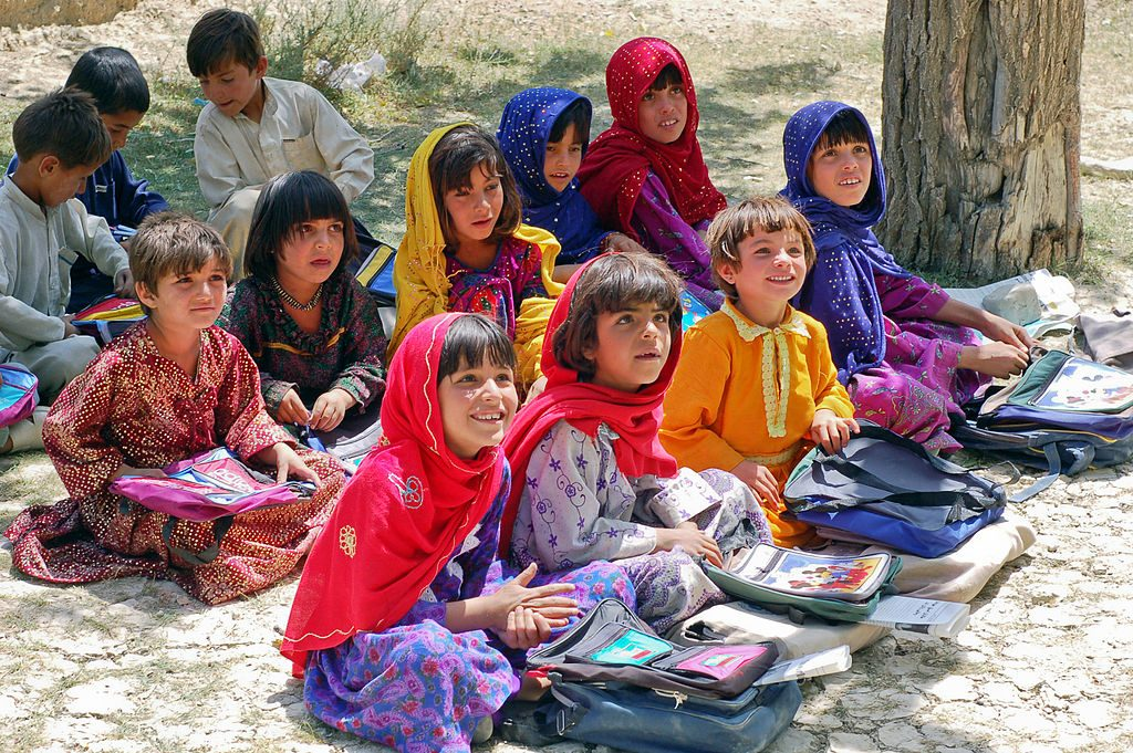 """Assembled girls and boys at school in Bamozai, near Gardez, Paktya Province, Afghanistan. The school has no building; classes are held outdoors in the shade of an orchard. (credit: Capt. John Severns, U.S. Air Force, license: Public Domain)"