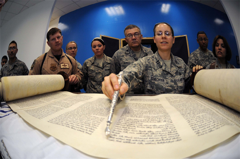 Reading [the Torah] JOINT BASE BALAD, Iraq -- Chaplain (Capt.) Sarah Schechter, 332nd Air Expeditionary Wing rabbi, describes the newly arrived Jewish Torah following a Torah dedication ceremony at Gilbert Memorial Chapel here March 21. A Torah is a big parchment leather scroll on which the Five Books of Moses are handwritten in Hebrew. For thousands of years, this is how Jews have maintained their law, teachings, religion and society. (U.S. Air Force photo/Senior Airman Elizabeth Rissmiller)