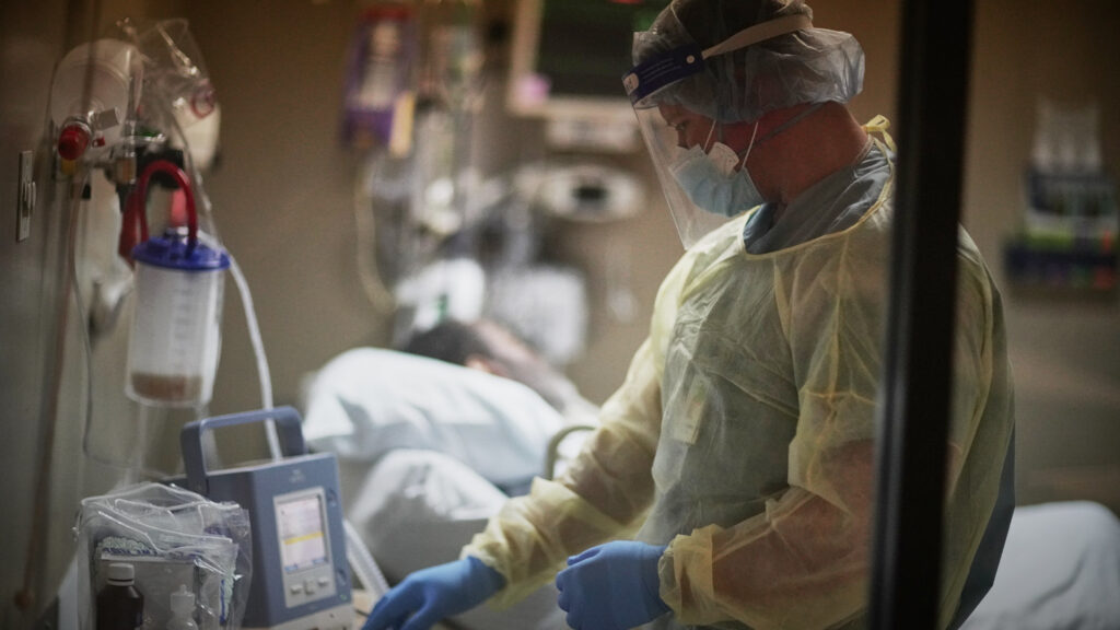 Lt. Cmdr. Michael Heimes checks on a patient connected to a ventilator at Baton Rouge General Mid City campus  (credit: Cpl. Daniel Betancourt, U.S. Navy, license: PD)