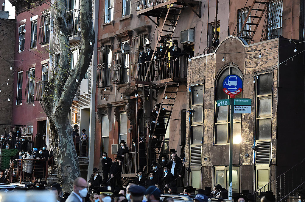 """Residents of the Williamsburg neighborhood of the Brooklyn borough of New York stand on fire escapes as hundreds of mourners gather Tuesday, April 28, 2020, to observe a funeral for Rabbi Chaim Mertz, a Hasidic Orthodox leader whose death was reportedly tied to the new coronavirus. The stress of the coronavirus' toll on the city's Orthodox Jews was brought to the fore Wednesday after Mayor Bill de Blasio chastised """"the Jewish community"""" following the breakup of the large funeral that flouted public health orders. (Todd Maisel via AP)"""