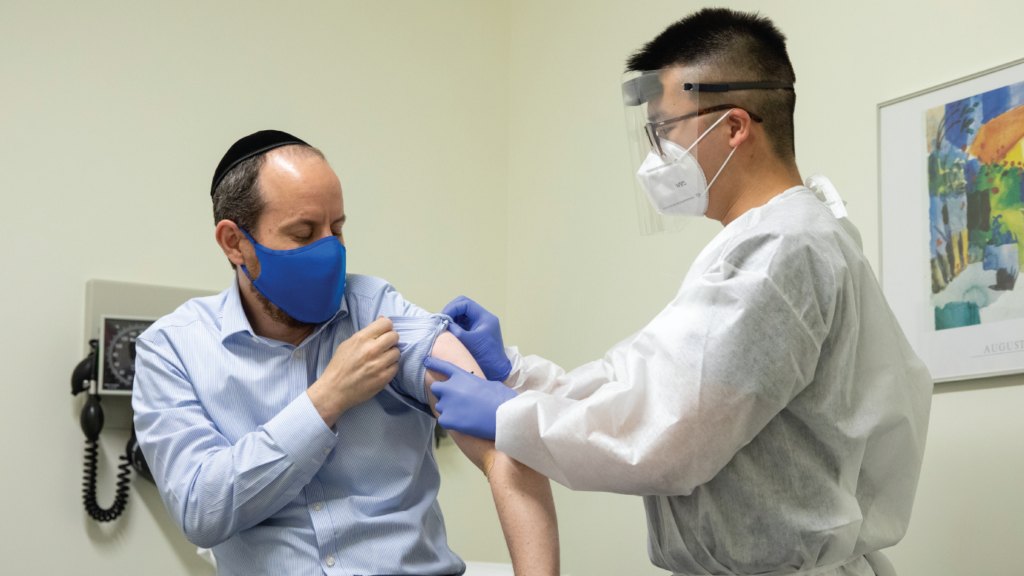 Rabbi Shmuel Herzfeld has his arm disinfected by Dr. Chao Wang during a clinical trial for a coronavirus vaccine. (Amanda Andrade-Rhoades/Getty Images)
