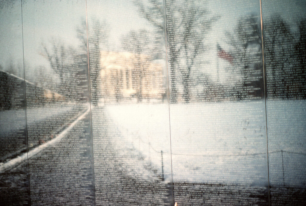 The Lincoln Memorial reflects from the face of the Vietnam Veterans Memorial after a snowfall. (credit: Don-Montgomery, license: Public Domain)