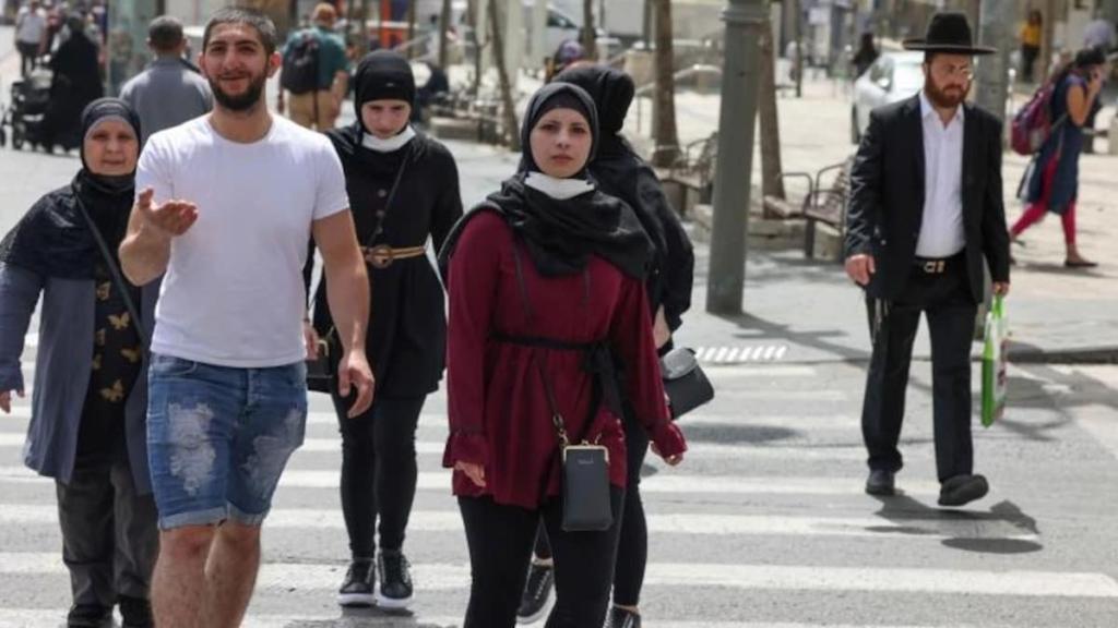 Israelis walk in Jerusalem without masks after the coronavirus restrictions were eased Sunday (Photo: AFP)