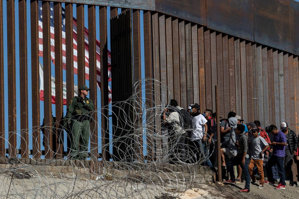 Central American migrants look through a border fence as a US Border PatRol agents stands guard near the El Chaparral border crossing in Tijuana, Baja California State, Mexico, on November 25, 2018. (Photo by GUILLERMO ARIAS / AFP) (Photo credit should read GUILLERMO ARIAS/AFP/Getty Images)
